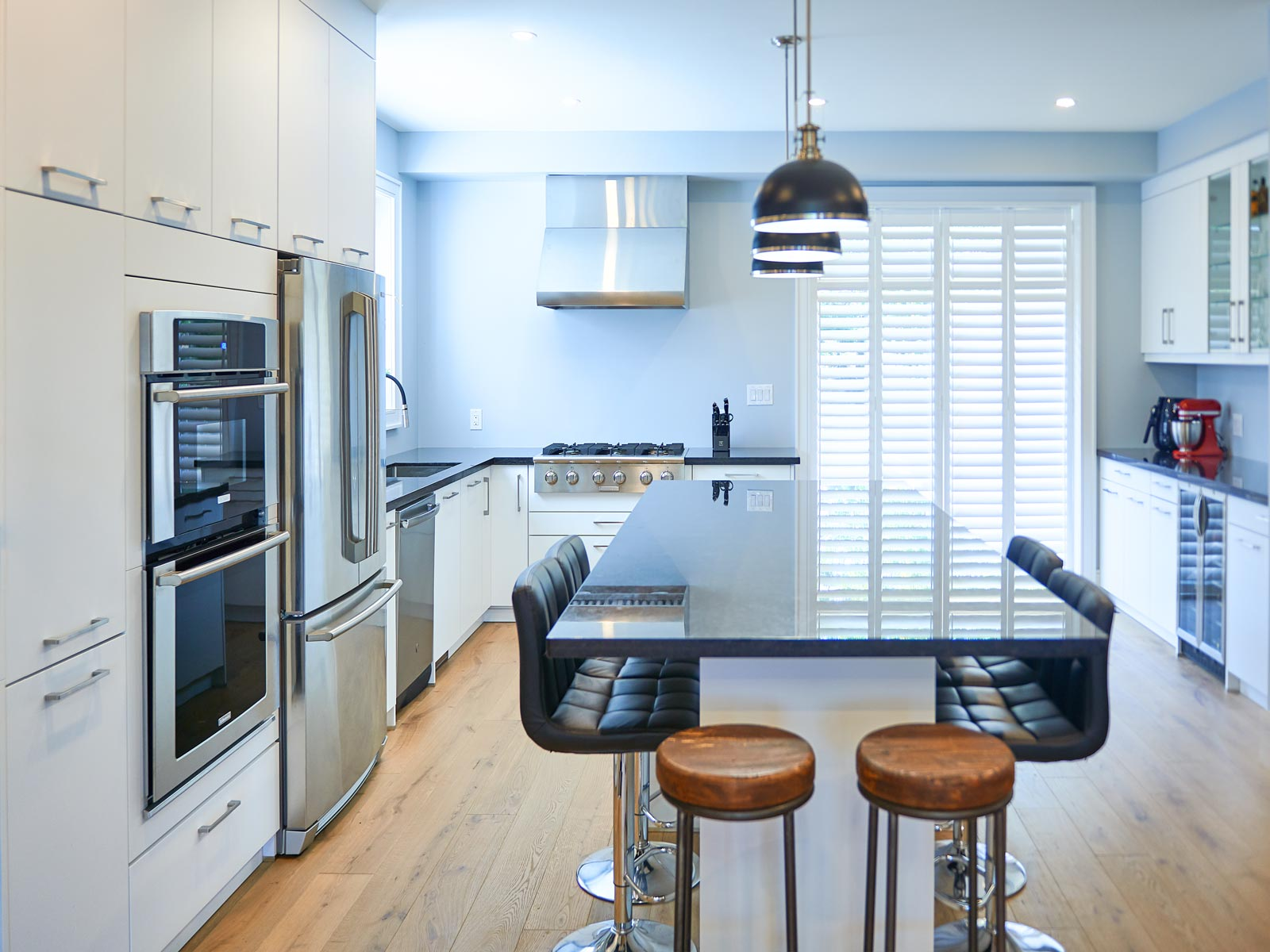 Snow white kitchen with glossy black countertop and Electrolux appliances in blue interior, Toronto