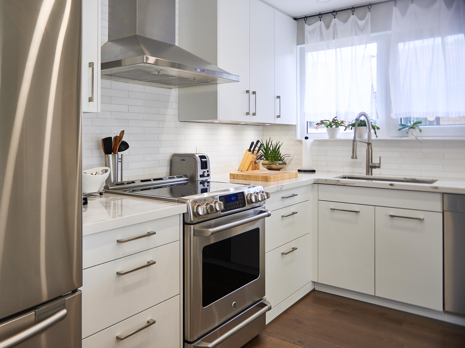 High gloss white kitchen with marble design countertop and appliances in 70th design style, Toronto