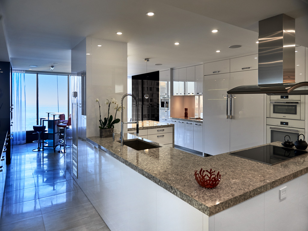Luxury kitchen interior with white cabinets, quartz countertop, top of the line Miele and Sub-Zero appliances in Toronto.